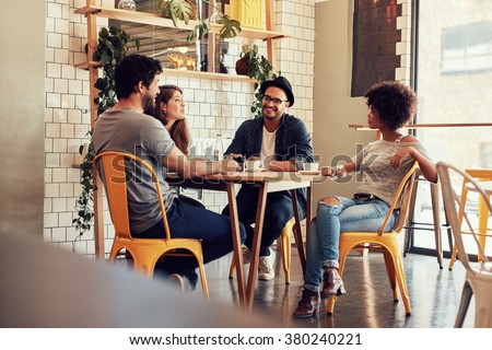 Young people sitting at a cafe table. Group of friends talking in a coffee shop. - stock photo