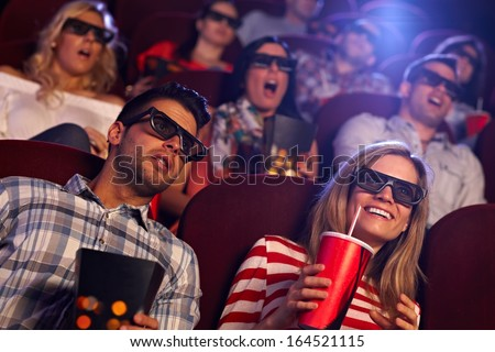 Young people sitting at cinema, watching 3D film, smiling. - stock photo