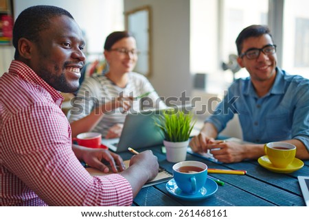 Young people sitting at table, drinking tea and studying - stock photo