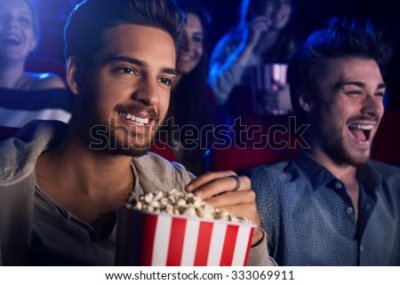 Young people sitting at the cinema, watching a movie and eating popcorn, two smiling men on foreground - stock photo