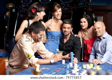young people sitting at the roulette casino table talking - stock photo