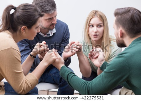 Young people sitting in a circle and holding hands on special group therapy - stock photo