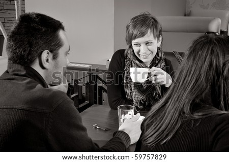 Young people sitting in cafe and talking - stock photo