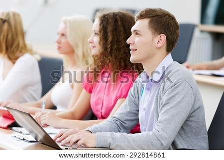 Young people sitting in classroom at lecture - stock photo
