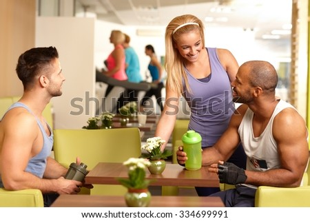 Young people sitting in gym bar, having break, talking, drinking refreshment. - stock photo