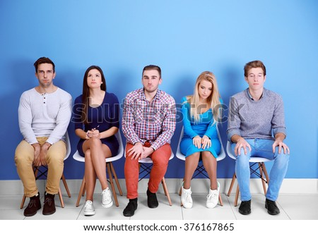 Young people sitting on a chairs in blue hall - stock photo