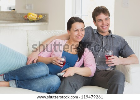 Young people sitting on the couch while watching television in the living room - stock photo