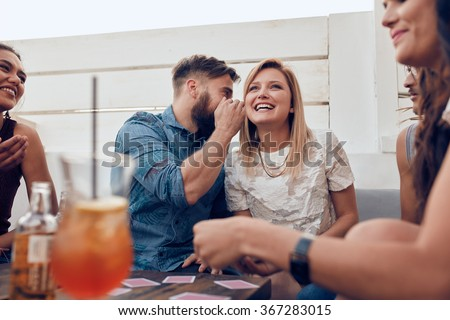 Young people sitting together in a party. Man whispering something in woman's ears. Sharing a secret. - stock photo