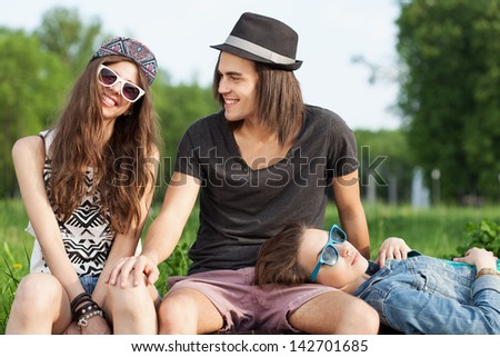 Young People Sitting Together On Park Bench. Outdoors