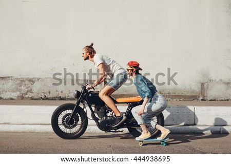 Young people skateboarding together on road. Young man and woman riding on a sunny day. - stock photo