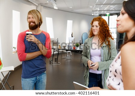 Young people standing in a gallery and contemplating artwork - stock photo