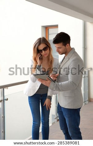 Young people standing in corridor, woman talking on mobilephone man using tablet. - stock photo