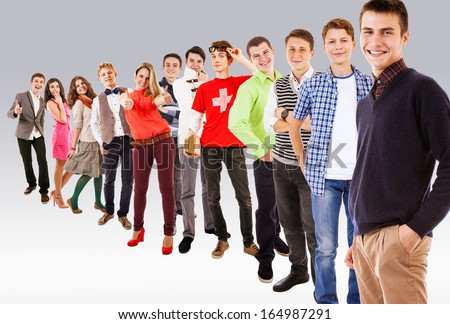Young people standing one behind other on rank - stock photo