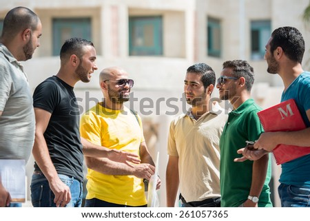 Young people standing together on university campus - stock photo