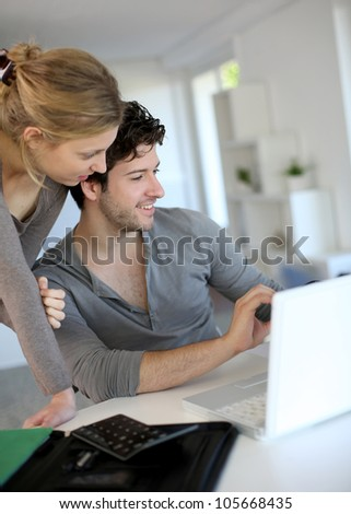 Young people studying from home with laptop computer - stock photo