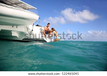 Young people swimming in the sea next to sailboat - stock photo