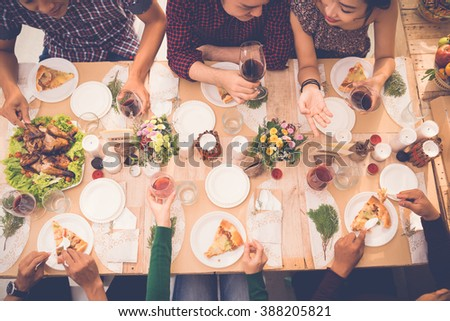 Young people talking and eating pizza at the table, view from above