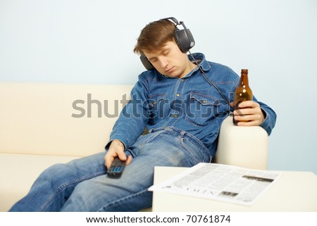 Young people traditionally relaxing at home after work - stock photo