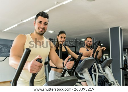 Young people training in eliptical exercises at gym - stock photo