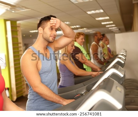 Young people training in running machine in gym. - stock photo