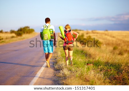 young people traveling hitchhiking. summer field - stock photo