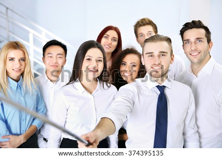 Young people using stick for group photo in office