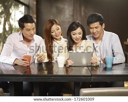young people using tablet computer during gathering in cafe. - stock photo