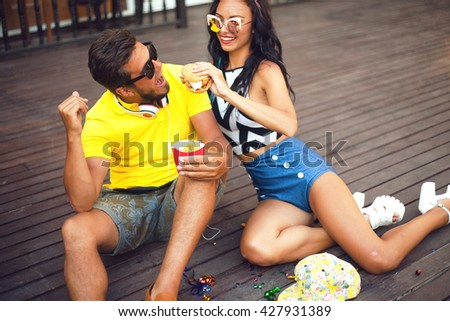 Young people walking outdoors. Sitting in the park and eat burgers and french fries,couple at sunglasses,young lovers looking at each other while eating fast food.bright summer outfit couple,romantic - stock photo