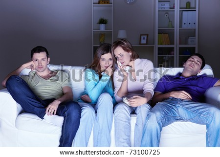 Young people watch a sad movie at home - stock photo