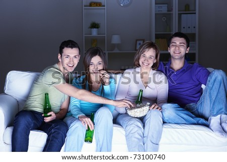 Young people watch TV at home
