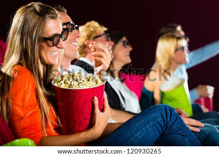 young people watching 3d movie at movie theater - stock photo