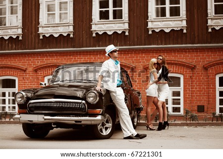 Young people with a retro car. - stock photo