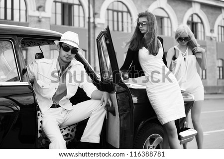 Young people with a retro car on a city street - stock photo