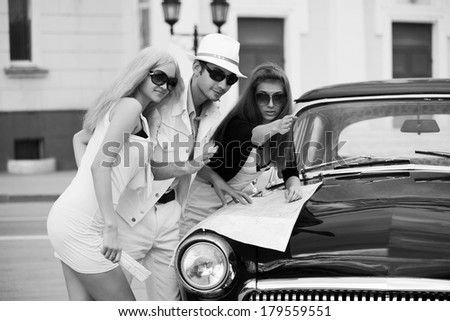Young people with a road map at the retro car  - stock photo