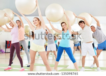 Young people with balls in fitness club