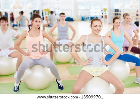 Young people with balls in fitness club - stock photo