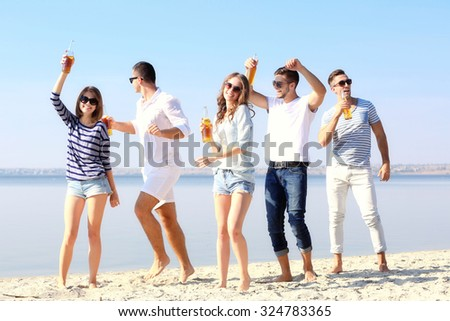 Young people with beer on the riverside - stock photo