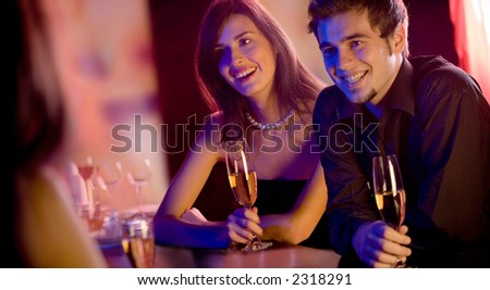 Young people with champagne glasses in restaurant, meeting - stock photo