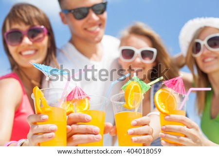 young people with cocktails in hand on the beach