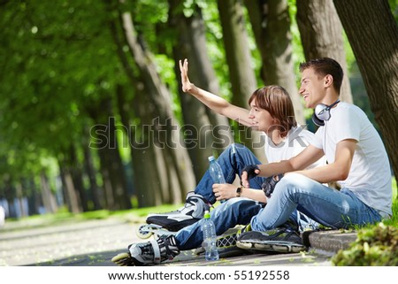 Young people with rollers have a rest on a border - stock photo
