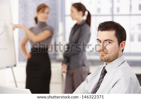 Young people working in bright office, man smiling in foreground, women chatting in background. - stock photo