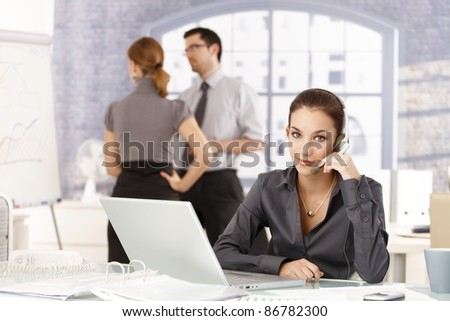Young people working in office, woman with headset in the foreground, colleagues having discussion in the background.? - stock photo