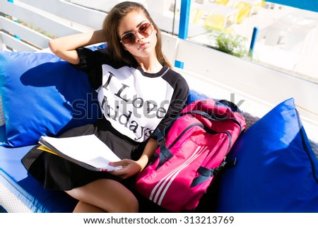Young perfect woman sitting on the floor white urban cafe wearing sportive top and shorts.Slim tan amazing body.Backpack.Fluffy Hairs.Full lips.Hipster girl,school uniform,young student study  - stock photo