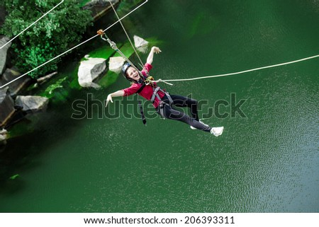 Young perfect woman sliding on a zip line in an adventure park above water. - stock photo