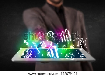Young person holding white tablet with graph and chart symbols - stock photo