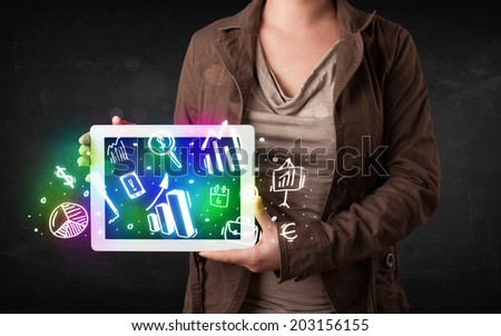 Young person holding white tablet with graph and chart symbols