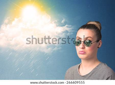 Young person looking with sunglasses at clouds and sun concept on blue background - stock photo