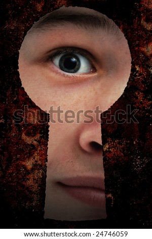 Young person peeping through an key hole - stock photo
