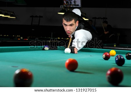 Young person playing snooker in a club - stock photo