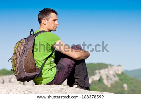 Young person relaxes on hiking in mountains - stock photo